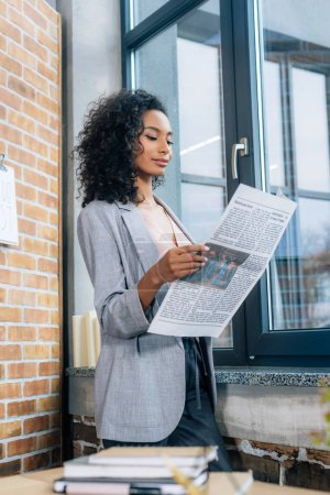 Photo for Beautiful african american Casual businesswoman reading Business newspaper in loft office - Royalty Free Image