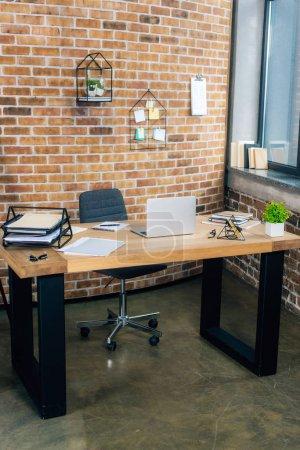 Photo pour Bureau avec ordinateur portatif et documents dans le bureau moderne de grenier avec le mur de briques - image libre de droit