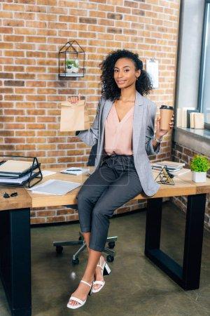 Photo pour Femme d'affaires afro-américaine occasionnel tenant sac de papier à emporter et café pour aller dans le bureau - image libre de droit