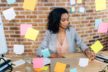 selective focus of Sticky Notes and african american Casual businesswoman at desk with laptop