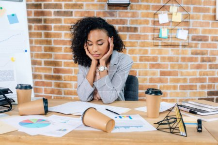 Photo for Tired african american Casual businesswoman at desk with coffee to go cups and charts in office - Royalty Free Image