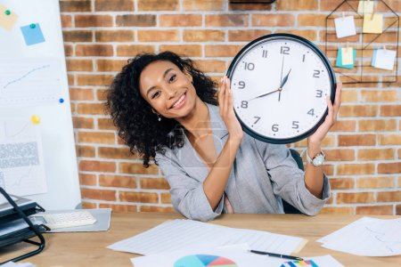 Photo pour Horloge de fixation de femme d'affaires occasionnelle d'Afrique de sourire dans le bureau de grenier - image libre de droit
