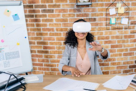 Photo for African american Casual businesswoman in virtual reality headset gesturing and sitting at office desk - Royalty Free Image