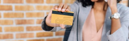 Photo for Panoramic of african american Casual businesswoman holding credit card in office - Royalty Free Image