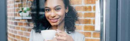 Photo for Panoramic shot of african american Casual businesswoman with coffee cup behind window - Royalty Free Image