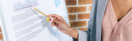 Photo for Panoramic shot of african american Casual businesswoman pointing with pencil at flipchart in loft office - Royalty Free Image
