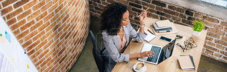 Photo for Panoramic shot of african american Casual businesswoman sitting at desk and using laptop - Royalty Free Image