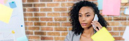 Photo pour Tir panoramique de l'Américaine africaine Casual femme d'affaires parler sur smartphone - image libre de droit