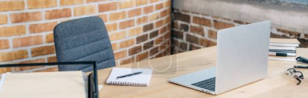 Photo for Panoramic shot of wooden desk with laptop, notebook and pen in loft office - Royalty Free Image