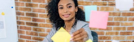 Photo for Panoramic shot of african american Casual businesswoman putting Sticky Notes on glass window in office - Royalty Free Image