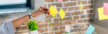 Photo for Panoramic shot of african american woman putting Sticky Notes on glass window in loft office - Royalty Free Image