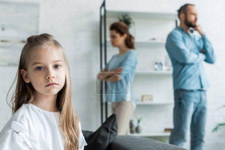 Photo pour Foyer sélectif de l'enfant triste regardant la caméra près des parents querelleurs à la maison - image libre de droit
