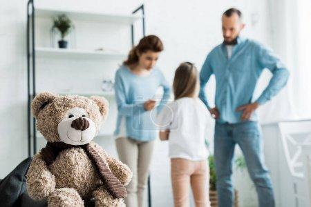 Photo pour Foyer sélectif de l'ours en peluche près de la famille querelle à la maison - image libre de droit