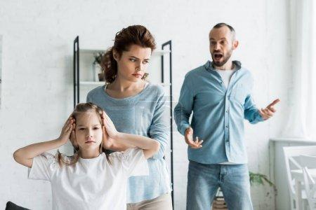 Photo pour Foyer sélectif de la mère couvrant des oreilles sur la fille tandis que l'homme criant à la maison - image libre de droit