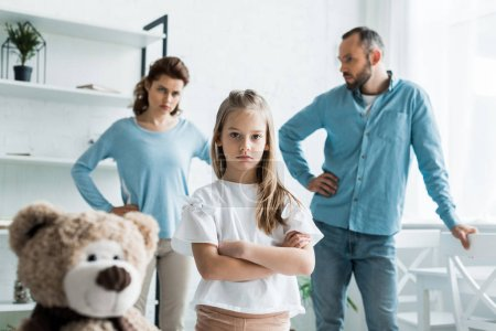 Photo for Selective focus of cute kid standing with crossed arms near teddy bear and parents at home - Royalty Free Image