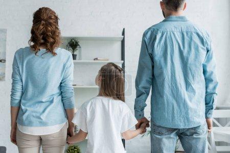 Photo pour Vue arrière du père et de la mère retenant des mains de la fille à la maison - image libre de droit