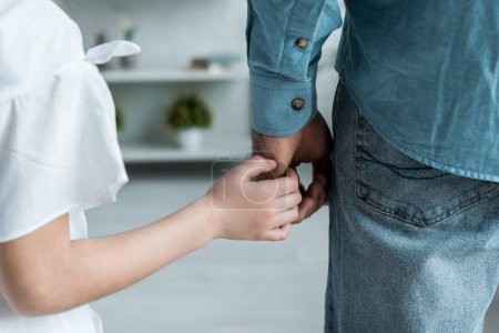 Photo for Cropped view of father and daughter holding hands at home - Royalty Free Image