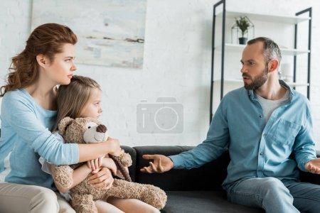 Photo pour Mère étreignant la fille avec l'ours de nounours et regardant le mari bouleversé à la maison - image libre de droit