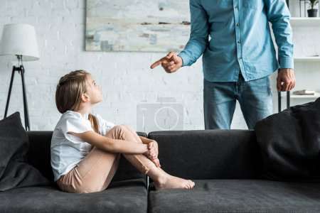 Photo pour Vue recadrée de l'homme pointant avec le doigt à l'enfant bouleversé s'asseyant sur le sofa à la maison - image libre de droit