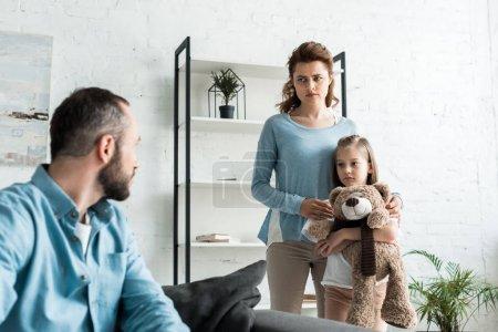 Foto de Enfoque selectivo de niño sosteniendo oso de peluche cerca de la madre mientras mira al padre - Imagen libre de derechos