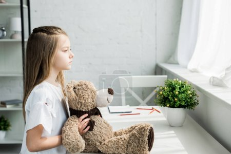 Photo for Cute kid holding teddy bear while standing near table at home - Royalty Free Image