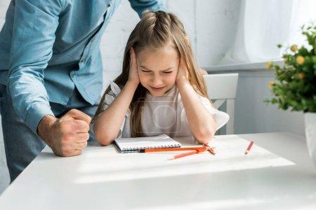 Photo pour Vue recadrée du père frappant bureau avec poing près enfant effrayé avec les yeux fermés à la maison - image libre de droit