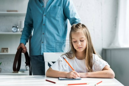 Photo for Cropped view of father holding belt and standing near cute kid holding pencil near notebook - Royalty Free Image