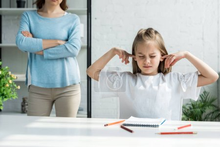 Photo for Cropped view of woman standing with crossed arms near kid covering ears at home - Royalty Free Image