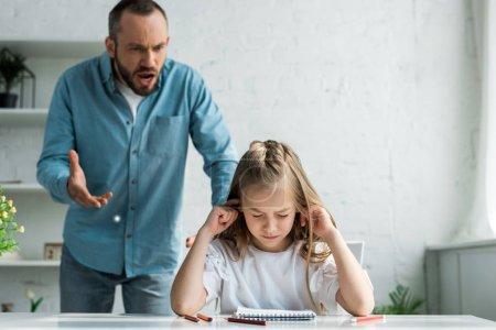 Photo pour Foyer sélectif de l'enfant couvrant des oreilles près du père criant à la maison - image libre de droit
