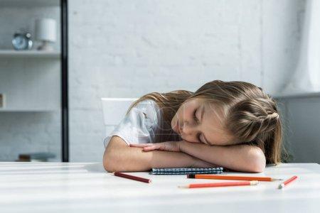 Photo pour Enfant fatigué avec les yeux fermés se trouvant sur la table près des crayons et du cahier - image libre de droit