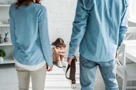 Photo pour Foyer sélectif de l'enfant effrayé s'asseyant sur l'étage près du père avec la ceinture et la mère - image libre de droit