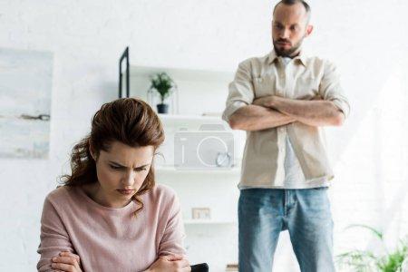 Photo pour Foyer sélectif de la femme offensée près de l'homme barbu avec les bras croisés - image libre de droit