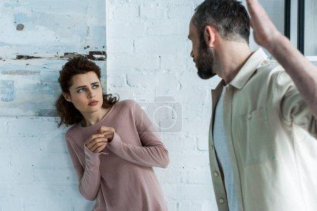 Photo pour Foyer sélectif de la femme effrayée regardant le mari agressif faisant des gestes à la maison - image libre de droit