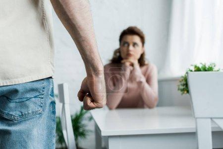 Photo pour Foyer sélectif de l'homme en colère menaçant de poing tout en se tenant près de la femme - image libre de droit