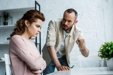 Photo pour Foyer sélectif de la femme s'asseyant avec les bras croisés près de l'homme menaçant avec le poing à la maison - image libre de droit