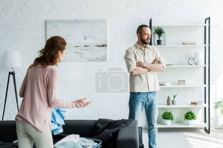 Photo for Brunette woman gesturing while looking at man standing with crossed arms - Royalty Free Image