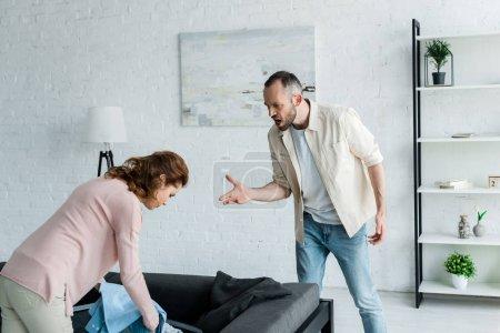 Photo pour Homme fâché faisant des gestes tout en regardant la femme emballant des vêtements à la maison - image libre de droit