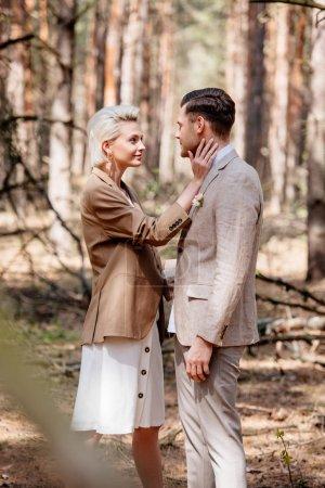 Photo pour Vue de côté de la mariée et de l'époux regardant l'un l'autre - image libre de droit