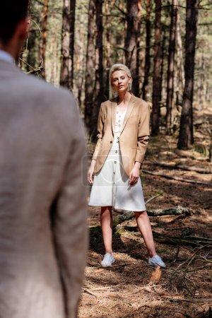 Photo pour Foyer sélectif de la mariée sylish attrayante regardant l'époux dans la forêt - image libre de droit