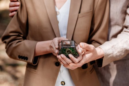 Photo for Cropped view of stylish couple holding box with wedding ring - Royalty Free Image