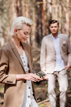 Photo for Selective focus of happy woman holding wedding ring and man looking at his woman in forest - Royalty Free Image