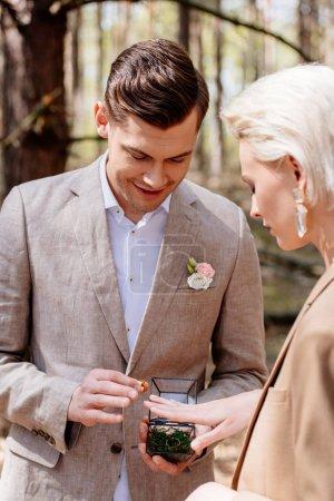 Photo pour Vue de côté de l'homme de sourire mettant sur l'anneau de mariage sur l'doigt de femme dans la forêt - image libre de droit