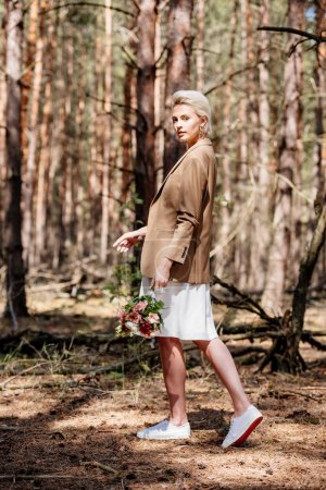 Photo for Full length view of stylish bride holding wedding bouquet in forest - Royalty Free Image
