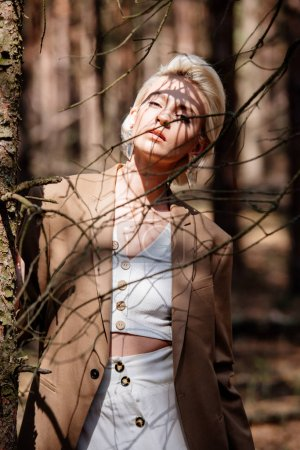 Photo for Stylish blonde young woman standing in forest and looking at camera - Royalty Free Image