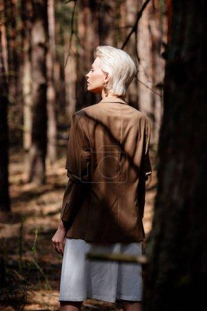 Photo pour Femme blonde pensive dans la veste brune restant dans la forêt - image libre de droit