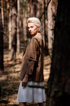 Foto de Elegant serious blonde woman looking at camera while standing in forest - Imagen libre de derechos