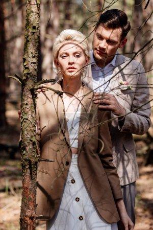 Photo pour Homme élégant embrassant doucement mariée blonde dans la forêt - image libre de droit