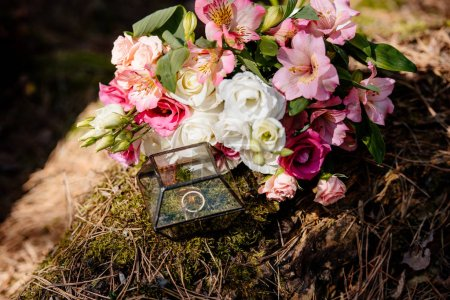 bouquet of fresh flowers and box with wedding rings