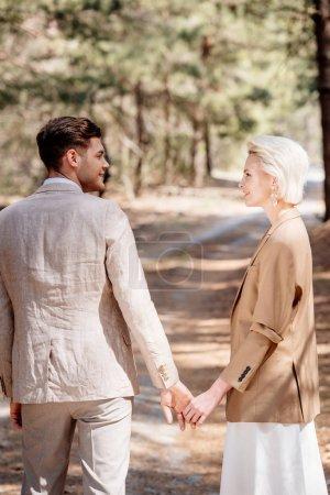 Photo pour Couples souriants élégants retenant des mains et regardant l'un l'autre dans la forêt - image libre de droit