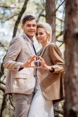 """Постер, картина, фотообои """"stylish smiling couple showing heart sign in forest"""""""